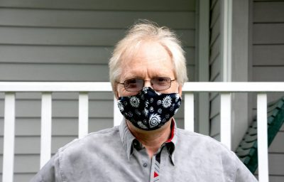 Uwe Täuber of the Department of Physics poses at his house, wearing a mask for COVID safety protocols.